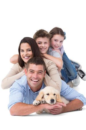 mujeres felices: Retrato de familia feliz acostado en uno encima del otro con el perro sobre fondo blanco Foto de archivo