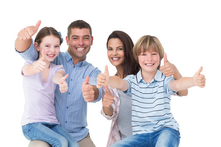 Portrait of happy family gesturing thumbs up over white background