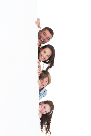 Portrait of happy family hiding behind billboard over white background