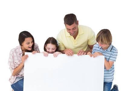 Familia de cuatro miembros feliz que mira la cartelera más de fondo blanco Foto de archivo