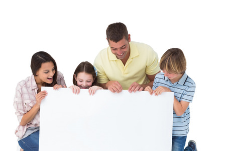 looking down: Happy family of four looking at billboard over white background