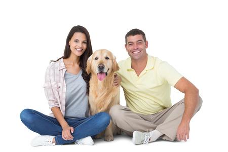 bonhomme blanc: Portrait d'un couple heureux avec un chien assis sur fond blanc