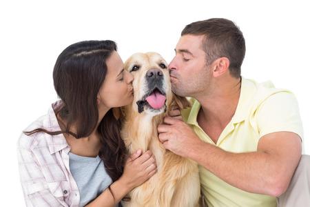 novios besandose: Pareja con los ojos cerrados que besa el perro sobre fondo blanco