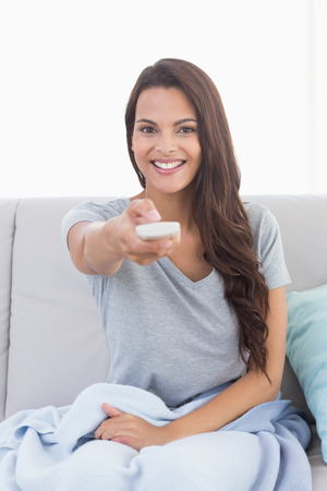 changing channels: Portrait of happy young woman changing channels on sofa at home Stock Photo