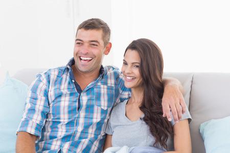 pareja viendo tv: Feliz pareja amorosa viendo la televisi�n en el sof� en casa Foto de archivo