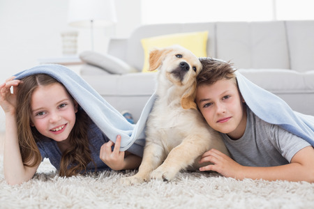 Portrait of cute siblings with dog under blanket in living room