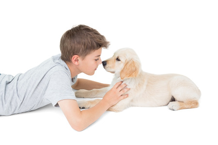 rubbing noses: Side view of boy rubbing nose with dog over white background