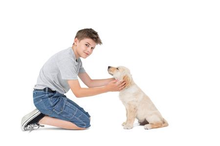 Full length portrait of boy stroking dog while kneeling over white background Stock Photo