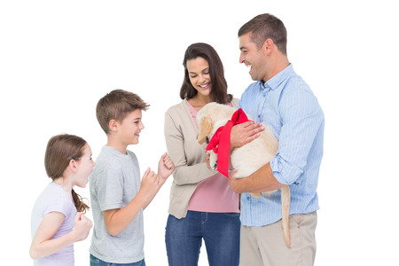 Happy mother and father gifting puppy to children against white background photo