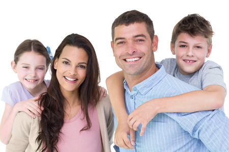 young boy smiling: Portrait of happy parents giving piggyback ride to children against white background Stock Photo