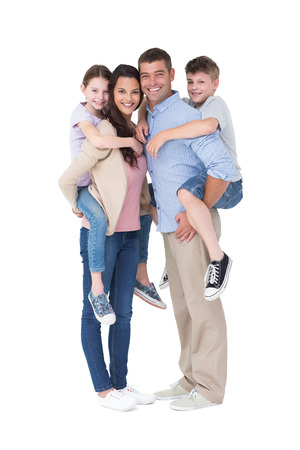 mom and dad: Full length portrait of parents giving piggyback ride to children over white background
