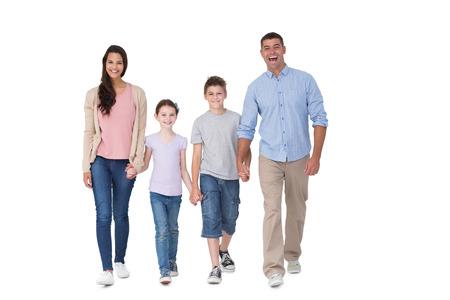 白い背景の上を歩いて幸せな家族の完全な長さの肖像画
