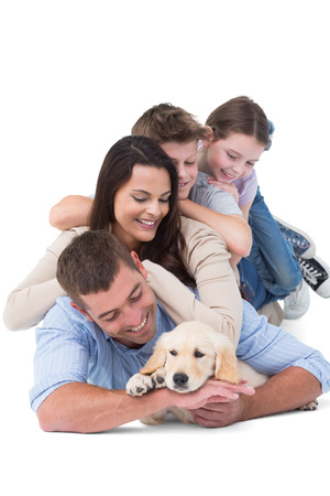 Happy family looking at puppy while lying on top of each other over white background