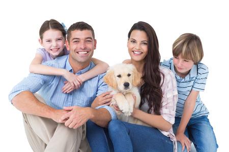 mujeres felices: Retrato de familia feliz con el perro lindo sobre fondo blanco