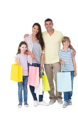 Portrait of happy family carrying shopping bags over white background Stock Photo