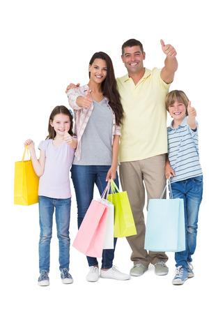 Portrait der glücklichen Familie mit Einkaufstüten gestikulieren Daumen hoch auf weißem Hintergrund Standard-Bild