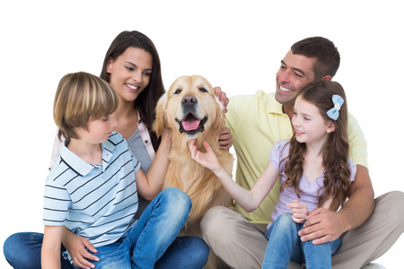 Happy family stroking dog over white background