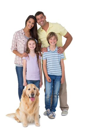 Portrait of happy family standing with dog over white background Foto de archivo