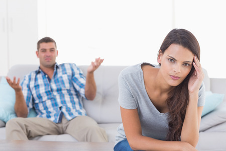 couple on couch: Portrait of woman suffering from headache while man quarreling at home Stock Photo