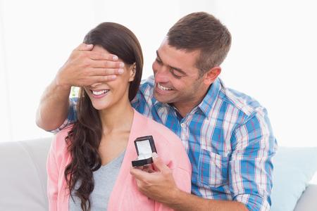 gifting: Hombre feliz que cubre los ojos womans mientras que regalar anillo en casa