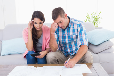 home finances: Worried couple calculating home finances at table in house