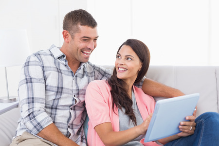 Happy couple with digital tablet sitting on sofa at home Stock Photo