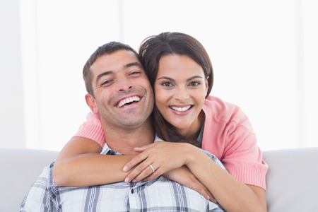 mid adult couple: Portrait of happy young woman embracing man at home Stock Photo
