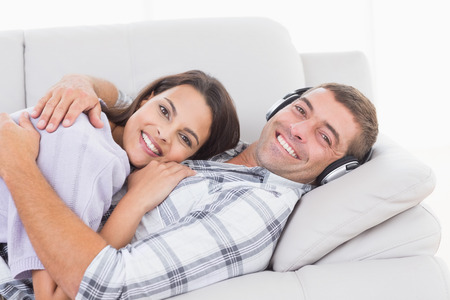 young handsome man: Portrait of happy man wearing headphones while embracing woman at home