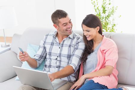 parejas enamoradas: feliz pareja de compras en l�nea en la computadora port�til con tarjeta de cr�dito en casa Foto de archivo