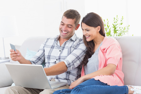 man holding money: Happy couple shopping online through laptop using credit card at home