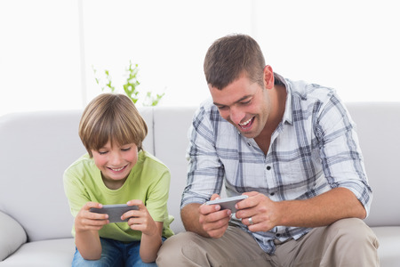 mobile: Happy father and son playing games on mobile phone at home Stock Photo