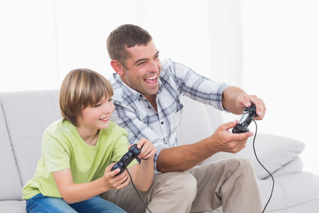 game: Happy father and son playing video game on sofa