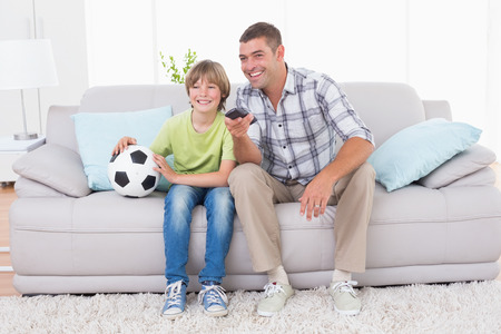 indoor soccer: Happy father and son watching soccer match while sitting on sofa at home