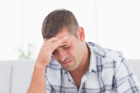 head pain: Man suffering from head pain at home