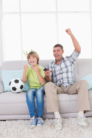 Happy father and son celebrating success while watching soccer match at home photo