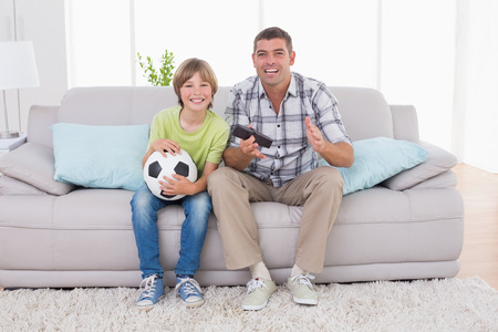 father and child: Portrait of happy boy watching soccer match with father on sofa at home