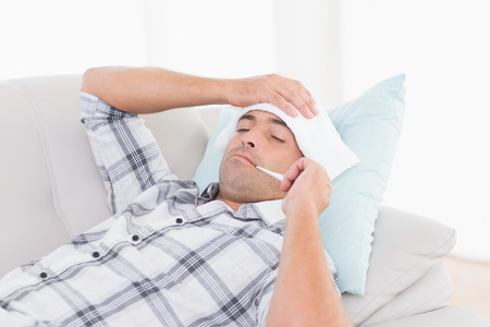 the sick: Sick man measuring temperature on thermometer while lying on sofa at home Stock Photo