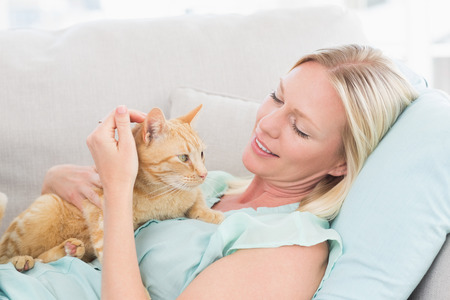 stroking: Young woman stroking cat while lying on sofa at home Stock Photo
