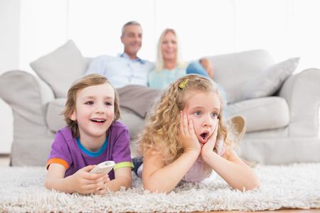 sorpresa: Ni�os sorprendidos viendo la televisi�n mientras los padres sentados en el sof� en casa Foto de archivo