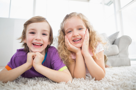 leaning on elbows: Portrait of happy siblings lying on rug at home