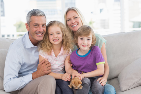 relaxing home: Portrait of happy family sitting together on sofa