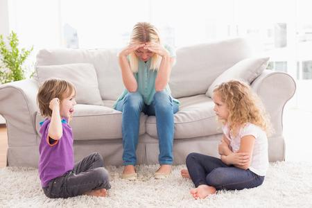 mujeres peleando: Malestar mujer sentada en el sofá, mientras que la hermana burlas hermano en casa Foto de archivo
