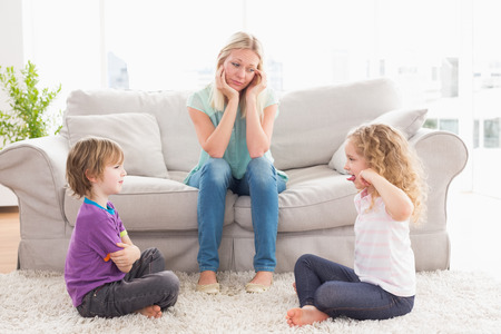 girl fighting: Upset mother looking at children fighting on rug at home Stock Photo