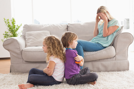 Angry siblings sitting arms crossed with upset mother on sofa at home