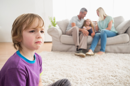 one child: Upset boy sitting on floor while parents enjoying with sister on sofa at home Stock Photo