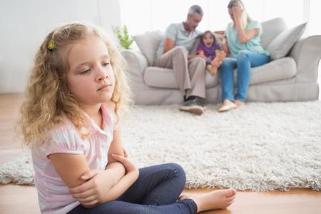 Malestar niña sentada en el piso mientras que los padres disfrutando con su hermano en el sofá en casa