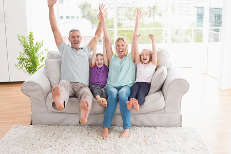 woman on couch: Happy family of four with arms raised sitting on sofa at home