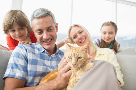 smiling cat: Happy family sitting with cat on sofa at home