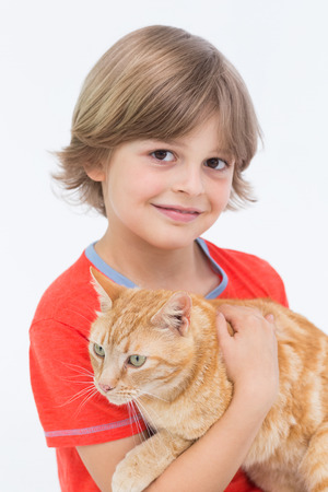 male bonding: Portrait of cute boy holding cat on white background