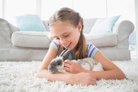 conejo: Muchacha linda que juega con el conejo mientras est� acostado en la alfombra en la sala de estar Foto de archivo